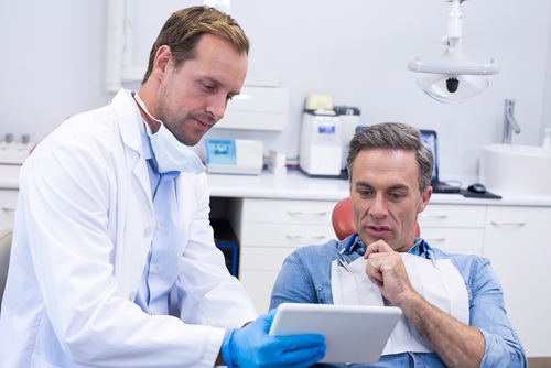 Young male dentist shows an older male patient the results of his dental exam on a tablet.