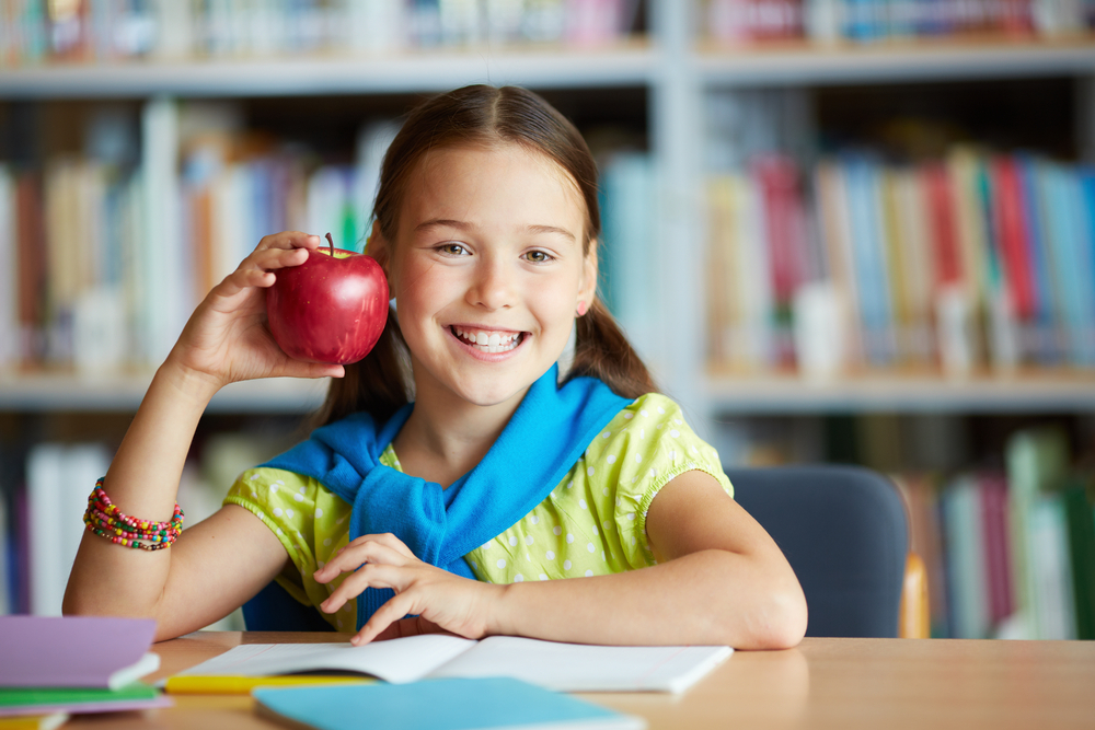 Young girl with brown hair in pigtails and sweater over her shoulder, holds apple in library, smiling.