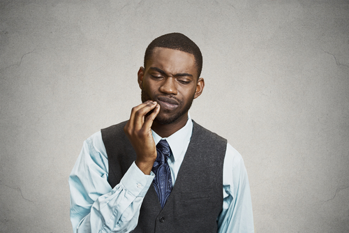 Young African-American executive touches his jaw as he winces from the pain of a toothache.