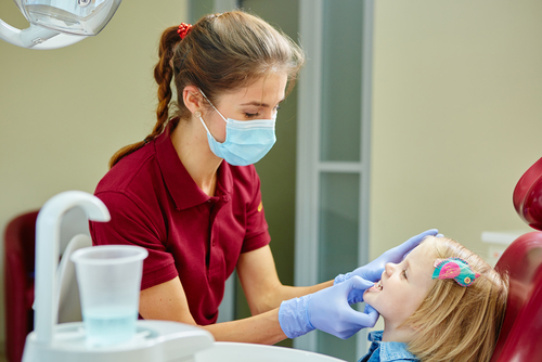Young female pediatric dentist with a red shirt examining a little girl's teeth.