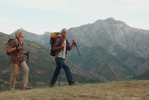 Happy older couple hiking in the mountains.