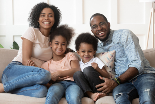 Happy black family nestles together on a couch. Left to right: Mom, young girl and boy, and Dad.