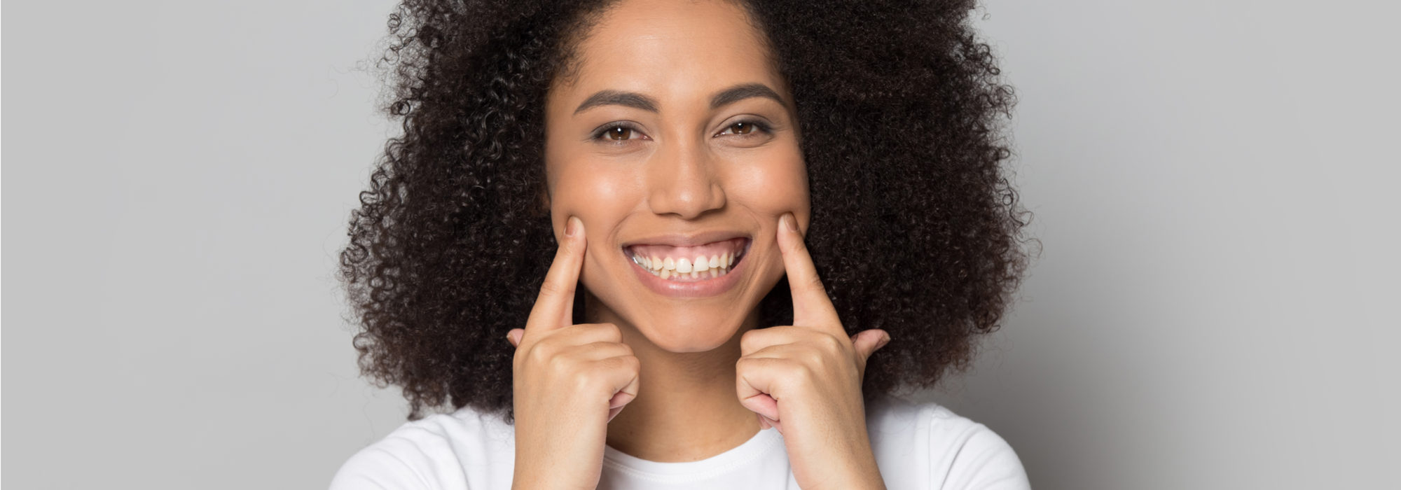 A young, lovely, African American female student with brown hair and brown eyes, wearing a white t-shirt points to her smile with both hands.