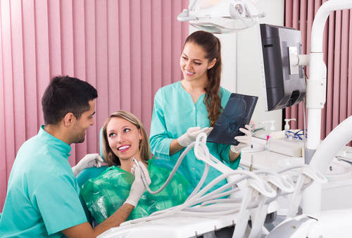 A Hispanic male dental student helps treat a young woman patient, while a female dental student with long brown hair examines an X-ray.
