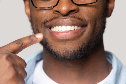 Man points to his perfect set of teeth.