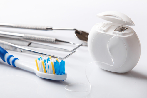 Toothbrush, dental instruments, and floss against a white background.
