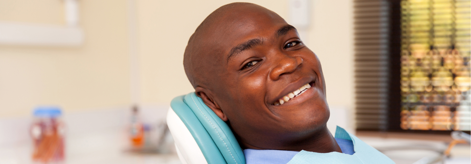 African-American male patient smiles as he sits in the dentist's chair.